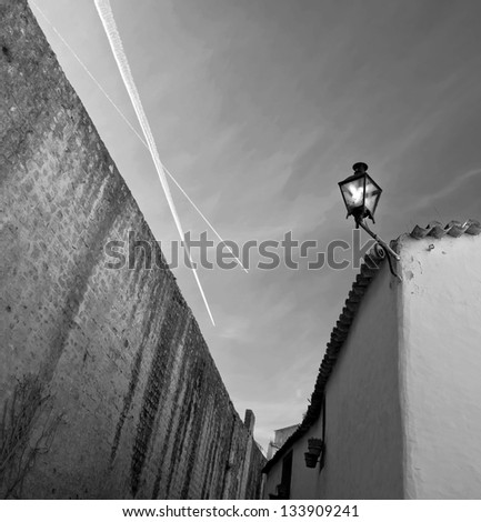 The narrow street along the fortress walls of the medieval town of Obidos - Portugal (black and white)