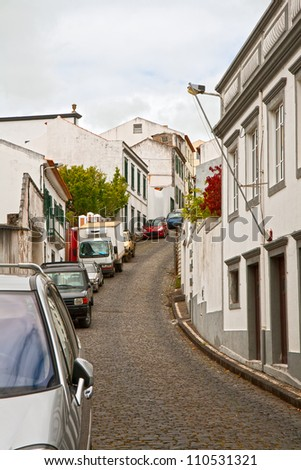 The narrow street on a steep slope with parked cars