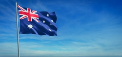 The National flag of Australia blowing in the wind in front of a clear blue sky. 3d illustration.