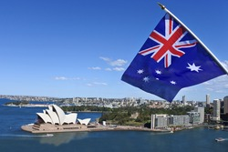The National flag of Australia flies above Sydney Harbor and the Opera house in Sydney Australia. No people. Copy space