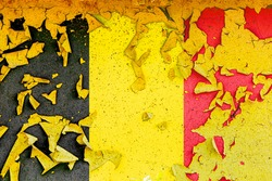 The national flag of Belgium is painted on an old metal wall with ragged paint. Country symbol.