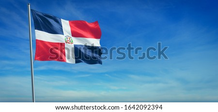 The National flag of Dominican Republic blowing in the wind in front of a clear blue sky. 3d illustration. Foto stock ©