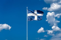 The national flag of Greece is waving in the clear blue Greek sky. The white cross symbolises Eastern Orthodox Christianity, the prevailing religion of Greece.