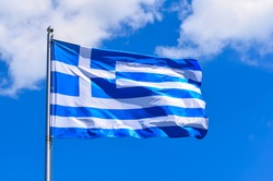 The national flag of Greece looks like 9 white and blue stripes with a cross on a background of blue sky in the summer afternoon.