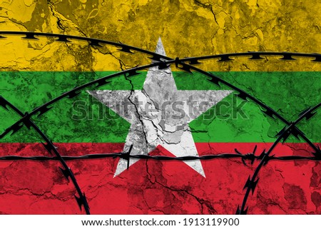 The national flag of Myanmar (Burma) painted on a grungy wall with Barbed wire in the foreground. Concept of the shut down in Myanmar after the military coup. 3D Illustration. 3d rendering Foto stock ©