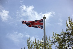The national flag of the United Kingdom (the Union Jack) fixed on a flagpole and waving, some tree branches are in the foreground, blue sky with white clouds is in soft-focus in the background