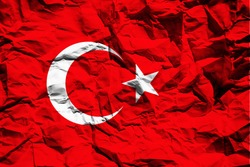 The national flag of Turkey on crumpled paper. Flag printed on a sheet. Flag image for design on flyers, advertising.