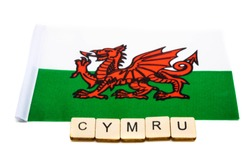 The national flag of Wales on a white background with a sign reading Cymru