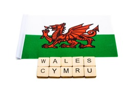 The national flag of Wales on a white background with a sign reading Wales Cymru