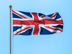 The national flags of the Great Britain Union Jack on the background of blue sky.