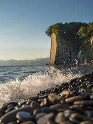 The natural attraction of the Black Sea is the Kiselev rock. Seascape. Summer day. Blue sea (with a wild pebble beach), sheer cliff at sunset. Vertically.
