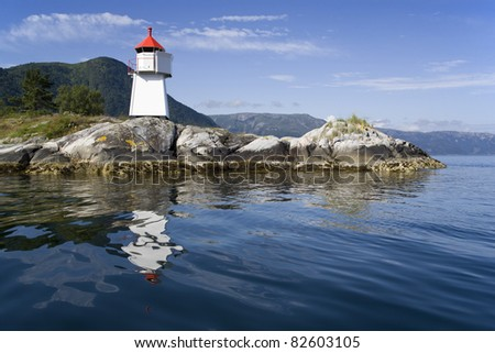 The nature of summer Norway. Reflections in fine pure water. Beacon on rocky coast