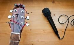The neck of a classic six-string guitar with headphones and a black microphone on a yellow board. guitar and accessories. creativity and playing the guitar