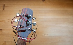 The neck of a classic six-string guitar with headphones on a yellow board. guitar and accessories. art and playing the guitar