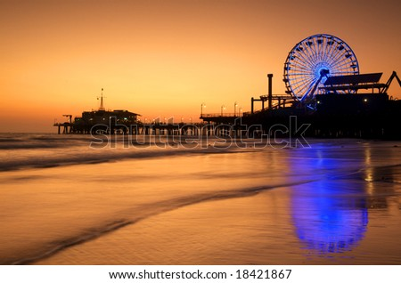 The Neon lit Ferris Wheel of Santa Monica Pier is reflected in the wet sand of the beach at Sunset.