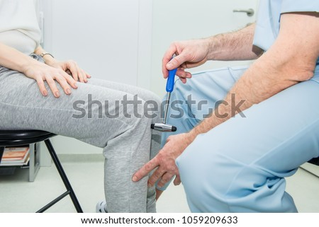 The neurologist testing knee reflex on a female patient using a hammer. Neurological physical examination. Selective focus, close up
