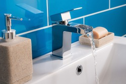 The new and modern steel faucet with the ceramic sink in the bathroom
