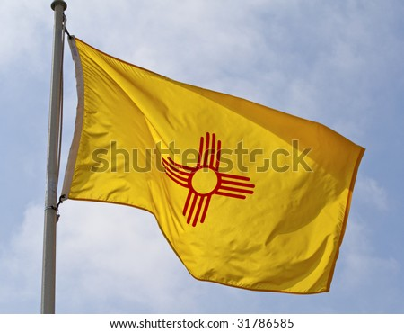 The New Mexico state flag flying in the wind.