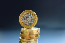 The new one pound coin balancing on the top of a pile.