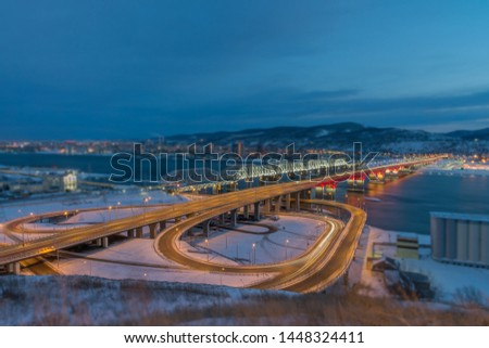 The new road bridge, illuminated by lanterns and moving cars, a beautiful reflection of the bridge in the Yenisei and the nearby railway bridge in the lights - a beautiful night landscape from above. #1448324411
