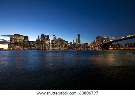 The New York City skyline at twilight w Brooklyn Bridge