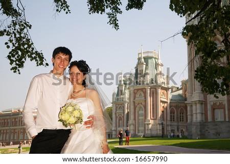 the newly married couple smiling near Tsaritsino palace at sunny day at Moscow