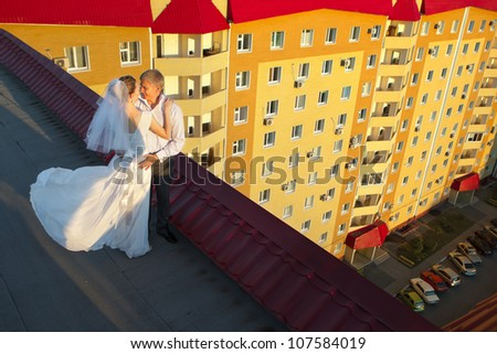 The newly married couple with cup of coffee standing on the roof of house in the morning