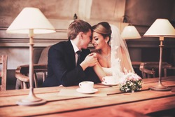 The newlyweds hug each other in an old cafe with lamps. The bridegroom embraces the bride against the backdrop of a beautiful arch. The newlyweds are pressed to each other with great love.