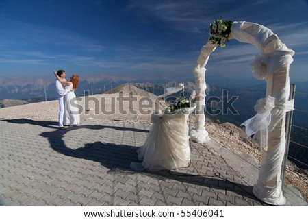 stock photo The newlyweds hugs near the wedding arch and altar against the
