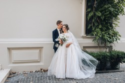 The newlyweds in love hug while standing on the alley in the city, against the background of a growing green bush. Wedding portrait of a young groom in a suit and a beautiful bride in a lace dress.
