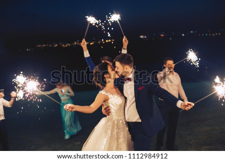 The newlyweds kiss and hold the sparkler