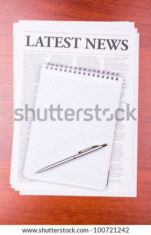 The newspaper LATEST NEWS on table and notepad