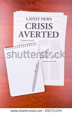 The newspaper LATEST NEWS with the headline CRISIS AVERTED and notepad