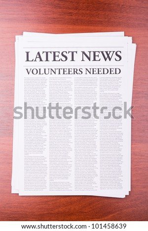 The newspaper LATEST NEWS with the headline VOLUNTEERS NEEDED