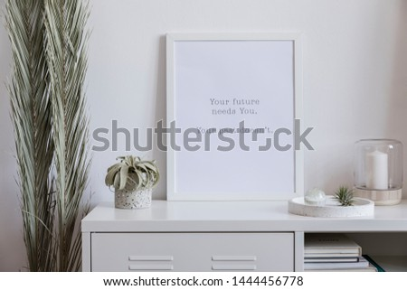 The nice scandinavian interior of living room with white mock up poster frame, air plant, palm leafs , candles, books and elegant accessories.  White background walls. Modern home decor. Template.