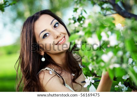 The nice young girl in blossoming trees