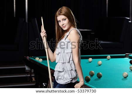 The nice young girl with cue at a billiard table