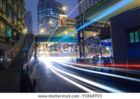 The Night move light trails on the modern building background in Highway