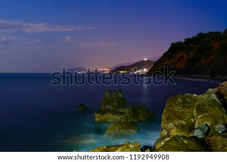 The night stones are washed by the surf. In the background, the lights of Alushta, Yalta and Ayu-Dag mountain. Long exposure