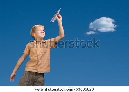 The nine-year boy starts the paper plane against the sky