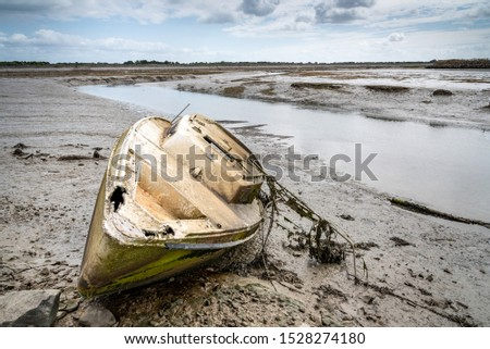 The Noirmoutier boats cemetery. The wreck of an old dismasted sailboat is stranded on the mud at low tide.