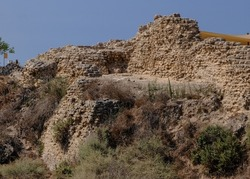 The north face fortification wall remains of Apollonia crusader castle, located on a high kurkar sandstone cliff facing the Mediterranean seashore of Herzliya city, Apollonia National Park, Israel.