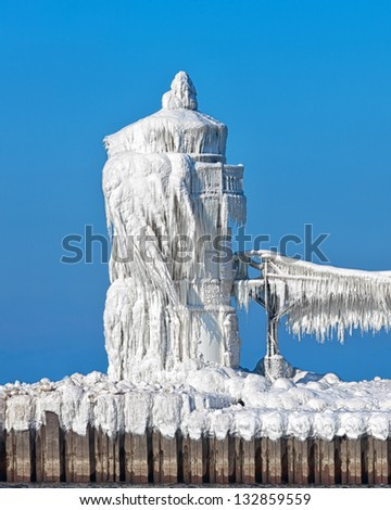 The North pier light in St. Joseph Michigan is shown encased in ice. Gusty winds splash Lake Michigan waves over the light in winter and leave the light looking like a beautiful ice sculpture