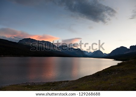 The north shore of Lake Sherburne looking west to large dark mountains at twilight with clouds reflecting the pink rays. Glacier National Park, Montana.