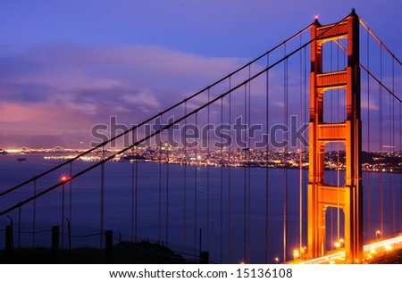 The North Tower of Golden Gate Bridge against the background of Bay Bridge and San Francisco skyline, shot from Battery Spencer (Marin Headlands) at dusk.