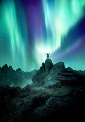 The Northern Lights dance across the night sky as a silhouetted man reaches up towards it. Photo composite.