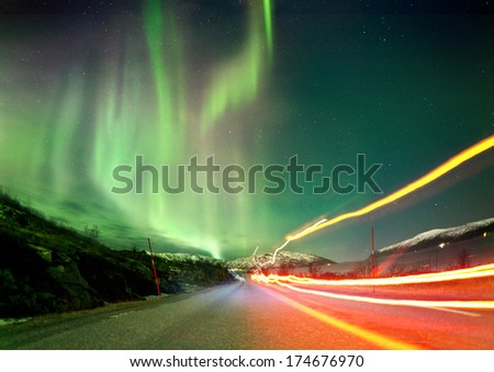 Stock Photo The Northern Lights in Norway landscape with red light trails on a road.