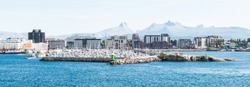 The Norwegian city of Bodo (Bodø) on a clear summer day, sees from the sea. Molo, port, harbor, cityscape with mountains in the background.