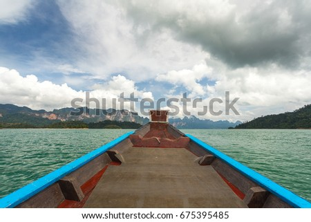 The nose of a long-tailed boat against the background of the karst rocks of Lake Cheo Lan #675395485