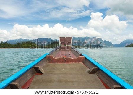 The nose of a long-tailed boat against the background of the karst rocks of Lake Cheo Lan #675395521